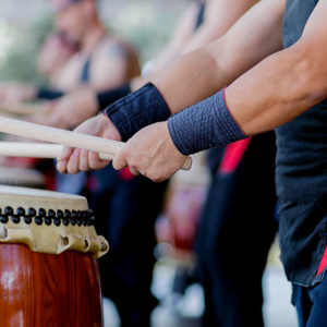 Hands with sticks beating drums